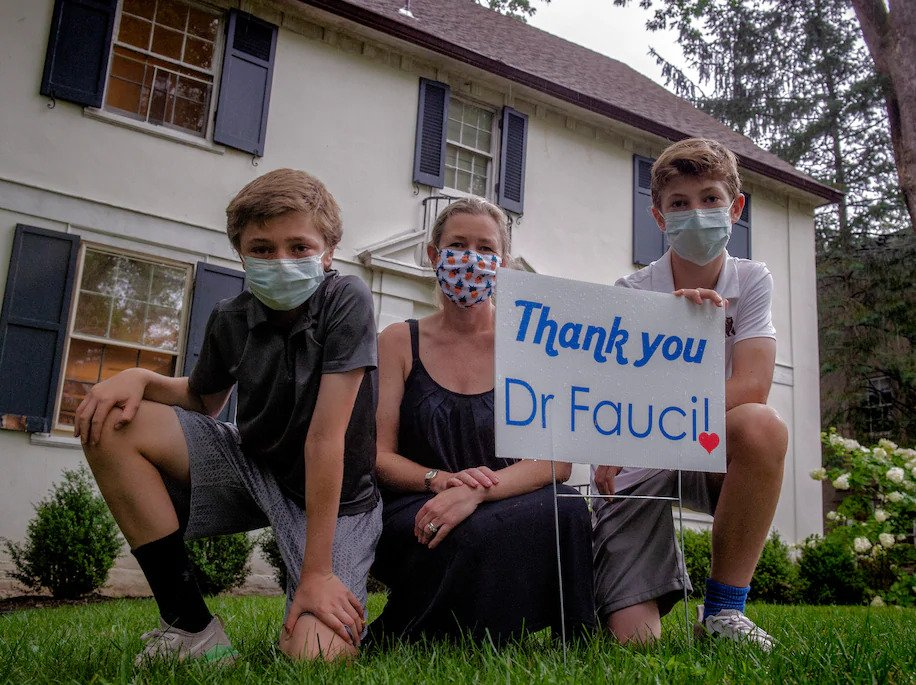 Ida Bergstrom and her sons Lars, 11, left, and Nils, 14, are selling yard signs to show support For Anthony S. Fauci, who is the nation's top infectious disease expert and one of their neighbors.